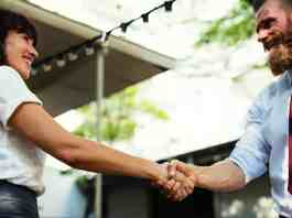 Two business people shaking hands outside