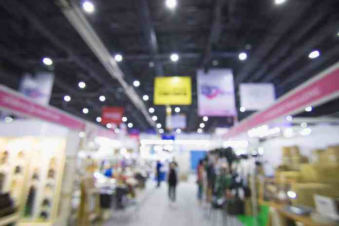 Blurred image of a trade show. Banners are clearly seen above booths in order to catch potential clients attention
