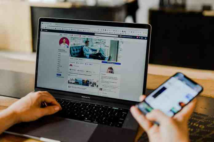 Facebook page of an entrepreneur's social media on desktop and mobile. Person using both a laptop and smartphone photo