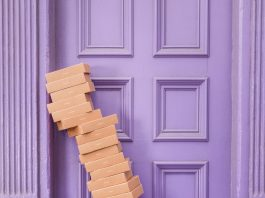 stack of shipping boxes leaning on a purple doorway