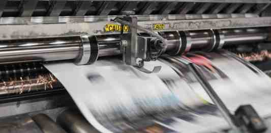 paper coming out of a printing press