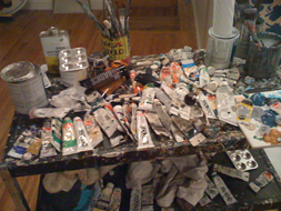 A melange of filled and half-filled paint tubes and brushes