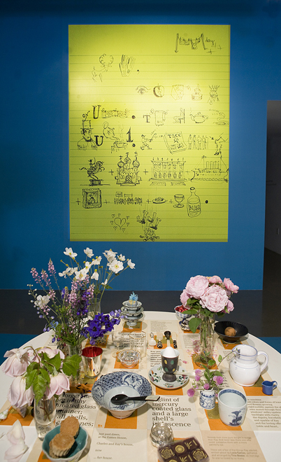 Close-up of rebus and dining table, showing objects and flowers picked in the garden typical of Ray. A poem by Charles's daughter Lucia appears typographically on the table surface.