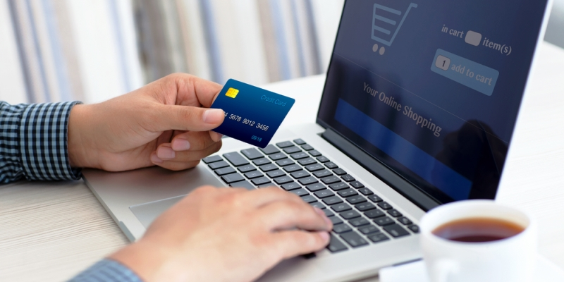 Person using a laptop to do an online shopping transaction with a credit card.