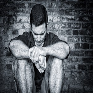 Sad young man sitting on the floor with a bricks background