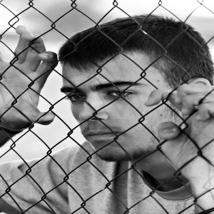Teenager behind a wired fence. Black and white photo