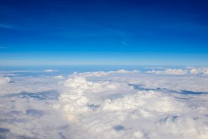 Photo of puffy clouds and blue sky from above the clouds.