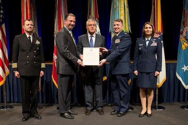 Dir. Ken Myers & USAF Col. John Cinnamon accept JMUA from Secretary Hagel.