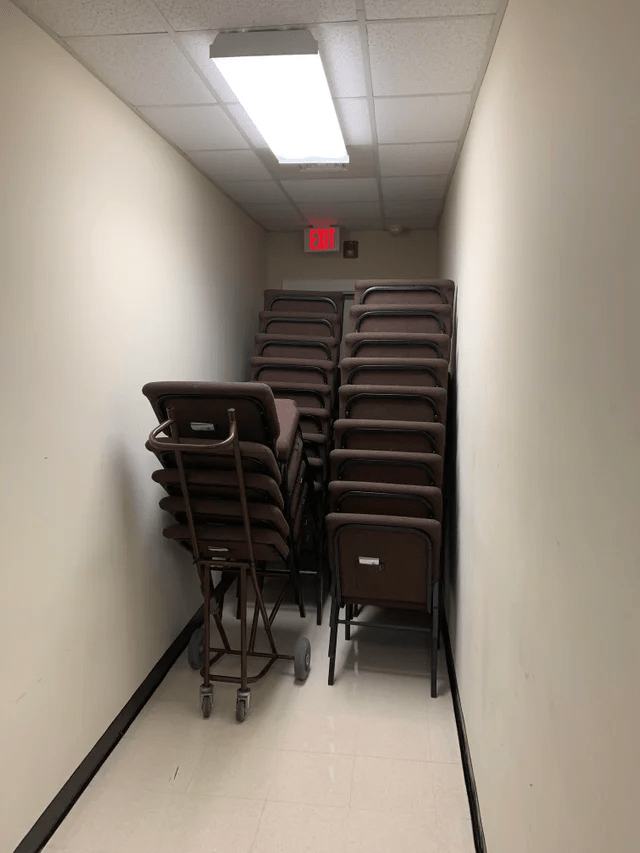 OSHA fail: Three stacks of chairs - one still in the cart - placed in front of the fire exit door.
