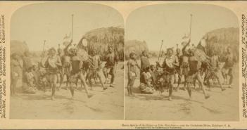 A photograph displays a group of Zulu warriors carrying shields and weapons and appearing to dance in front of a group of other Zulu.