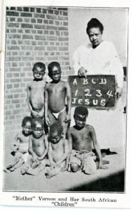 An adult woman stands next to 6 young children. The woman holds a chalkboard with the following text: A, B, C, D, 1, 2, 3, 4, Jesus.