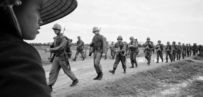A black and white photograph displays a line of U.S. Marines in uniform marching down a road. A Vietnamese person stands next to the road watching the soldiers.