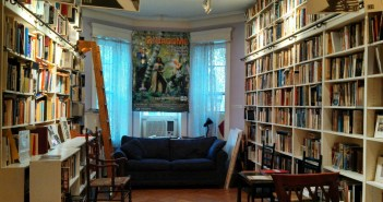 A color photograph shows a room with wall-to-wall bookcases and a couch under a window.