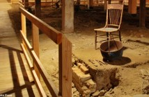 A photograph shows an underground room with a wooden chair and a bucket that appear very old.
