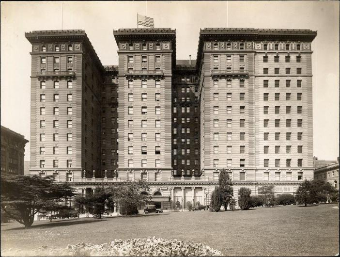 A photograph shows a multistory hotel building.