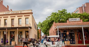 A horse-drawn carriage moves down the street in front of historic buildings.