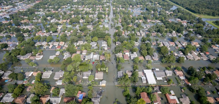 A photograph displays an aerial image of street flooding in Houston. The flooded area appears to be several residential neighborhoods.