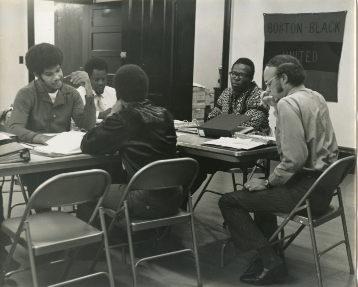 "A black and white photograph shows several men sitting around a table working on papers on the table. A banner in the back reads ""Boston Black United."""