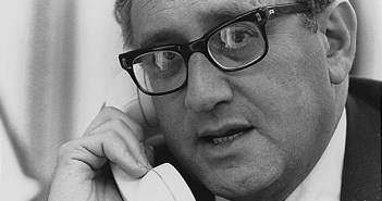 Henry Kissinger speaks into a telephone.