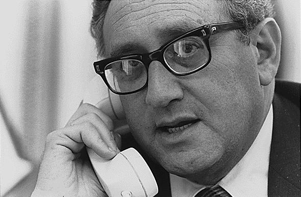 Henry Kissinger speaks into a telephone.