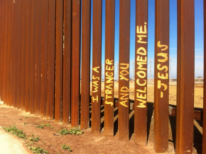 "In yellow paint, the words ""I was a stranger and you welcomed me - Jesus"" are written on brown, rusty fence slats."