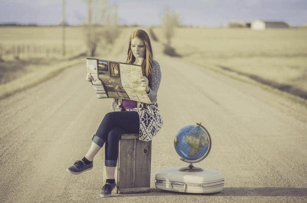 mujer sentada maleta carretera mapa