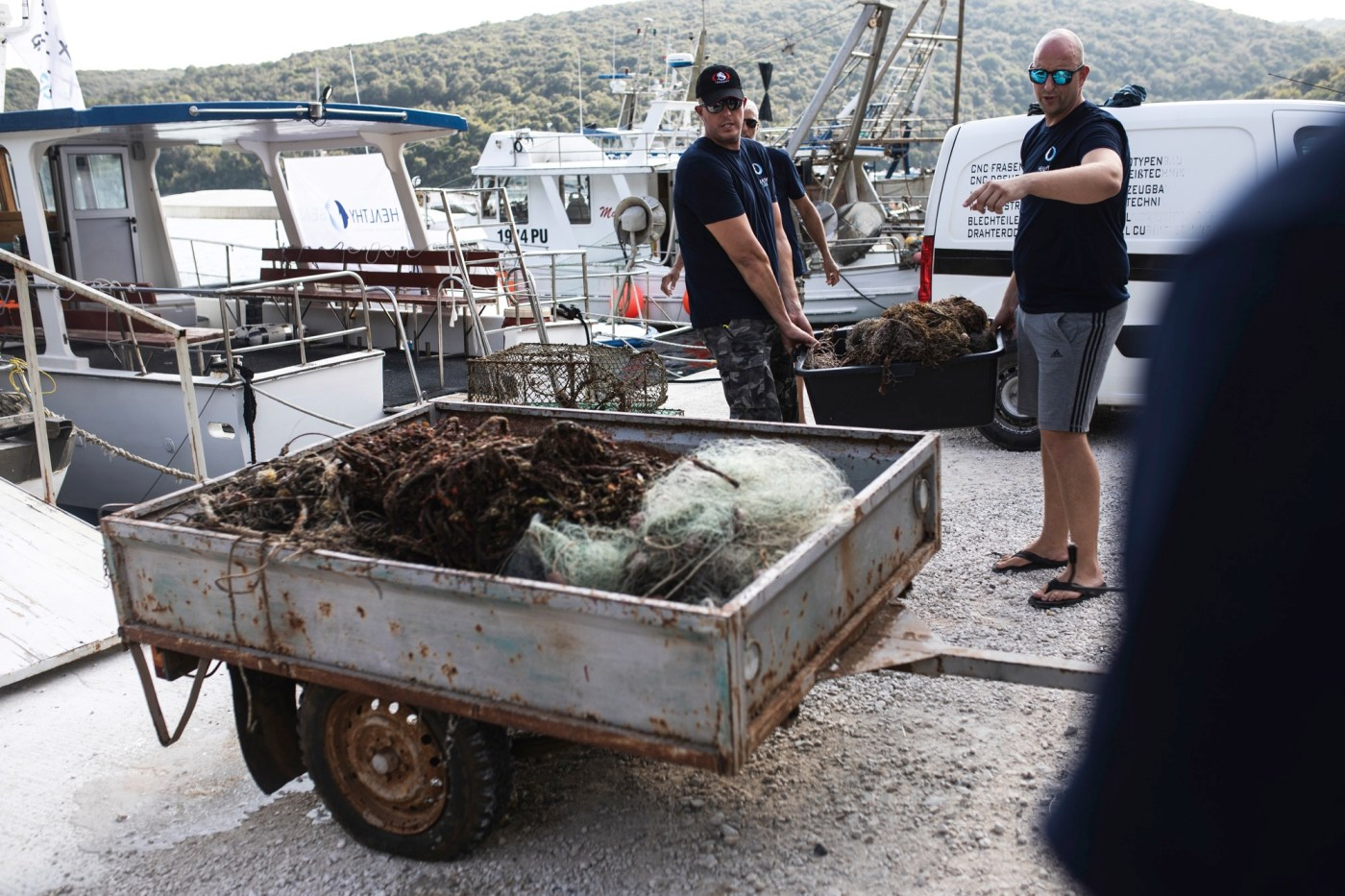 Healthy seas divers cleaning up discarded fishing net from ocean