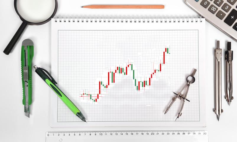 Un cahier avec des graphique de trading sur un bureau entourer de matériel de dessin