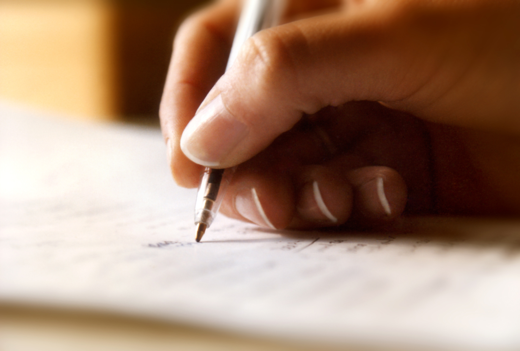 A woman's hand writes with a pen