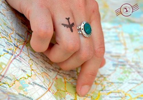 Tatuaggio di un aeroplano sul dito