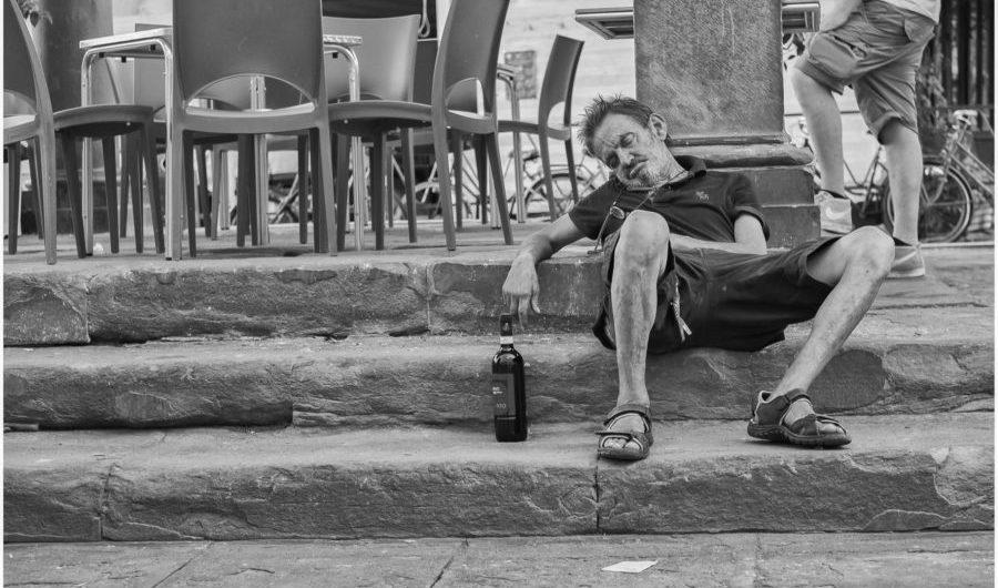 Uomo addormentato sui gradini della Loggia del Pesce in piazza del CIompi a Firenze