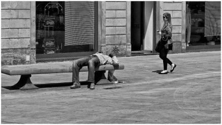 Un giovane sdraiato su una panchina in piazza Santa Maria Novella