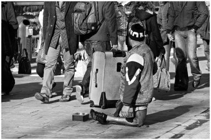 Un uomo con le gambe deformi chiede l'elemosina ai turisti, che procedono trascinando i trolley senza guardarlo.