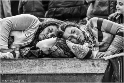 Due donne con in mano il bicchierino di tè freddo con cui chiedono l'elemosina dormono sdraiate, testa contro testa, sulle panchine di piazza Santa Maria Novella