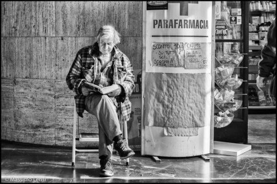 Ugo seduto a leggere in Stazione. © Massimo Lensi