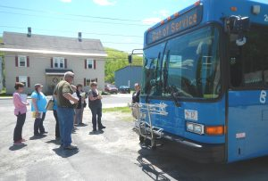 Rural travel training students standing by blue bus
