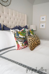 An eclectic bedroom with navy pillows, schumacher pillows, leopard lumbar pillow, Black and white greek key bedding, tufted wingback upholstered bed. Agate art and double gourd lamp. white curtains, Sherwin Williams Respose Gray