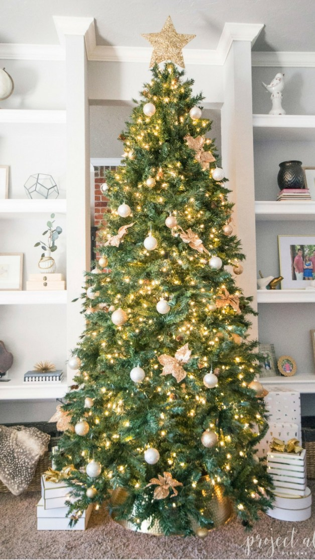 Modern Glam Christmas tree with gold ornaments, brass tree collar, glittered magnolia leaves and white and gold Christmas gifts add the perfect touch to these custom built-ins.