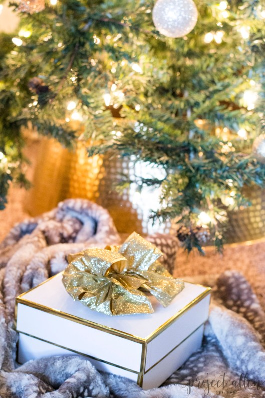 Holiday Gift Guide, Christmas Tree. Christmas Gift Ideas, white and gold gift box, gold bow, and an antelope throw blanket create a glam Christmas look. Find the perfect Christmas Gift Ideas For Everyone On Your List