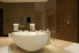 Unique style bathroom with light coloured gloss flor tiles and dark painted walls with dark mozaic tiles for feature wall inside shower area. Framless shower screen between oval bath and open shower
