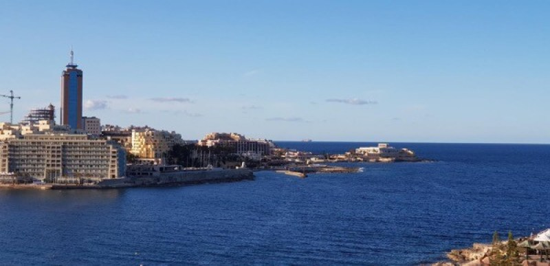 there is a giant MSC ship in the distance outside the northeast coast of Malta.