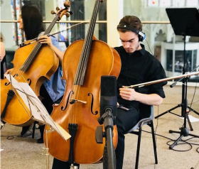 A male cellist in an orchestra