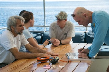 Team morning planning session while Scuba diving MIA crash sites aboard the Taka Live a Board scuba diving ship - Project Recover and BentProp Project are committed to bringing the MIA home. Photos by Harry Parker Photography.com