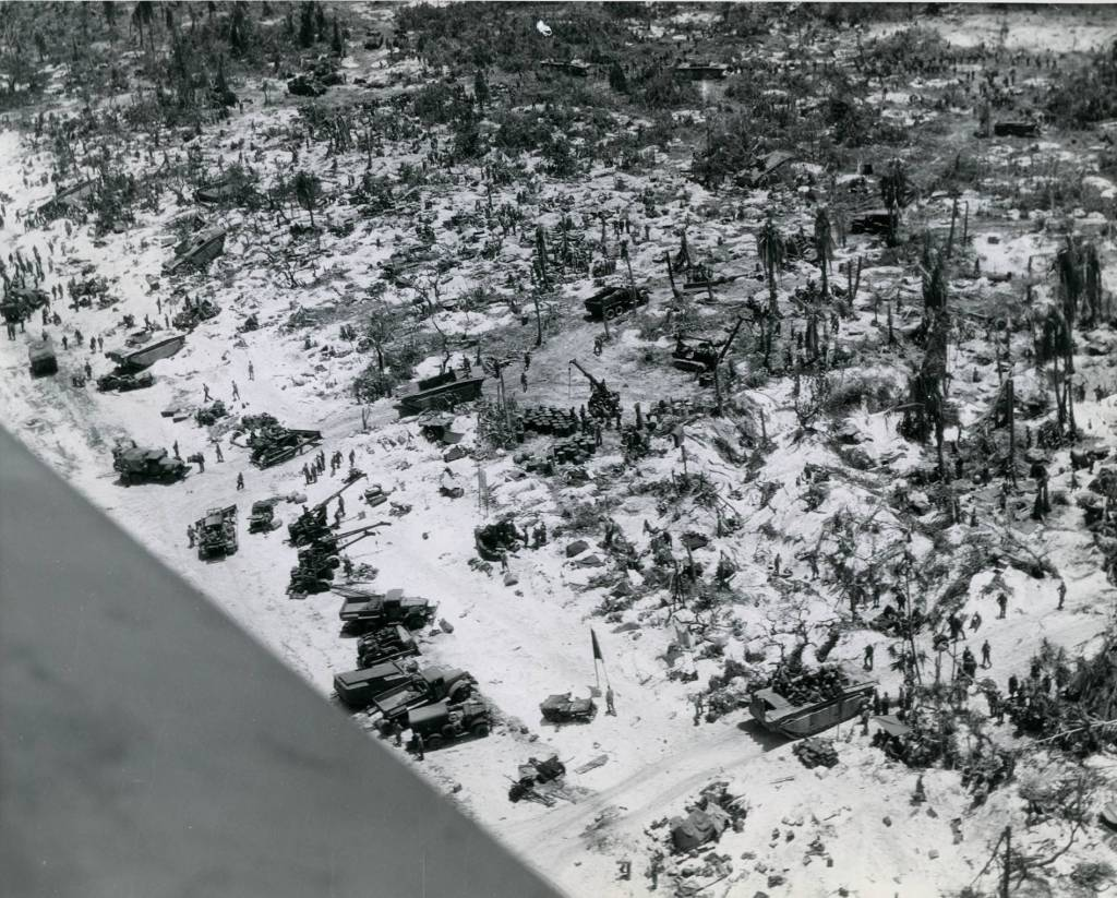 US Marines move supplies ashore across the beachhead on Peleliu in late September 1944. What appears to be water in the lower left is the wing of the airplane.