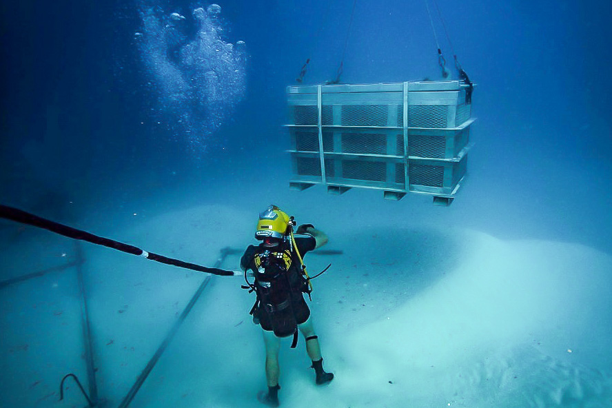 Navy Diver working underwater ocean MIA recovery Palau basket of remains