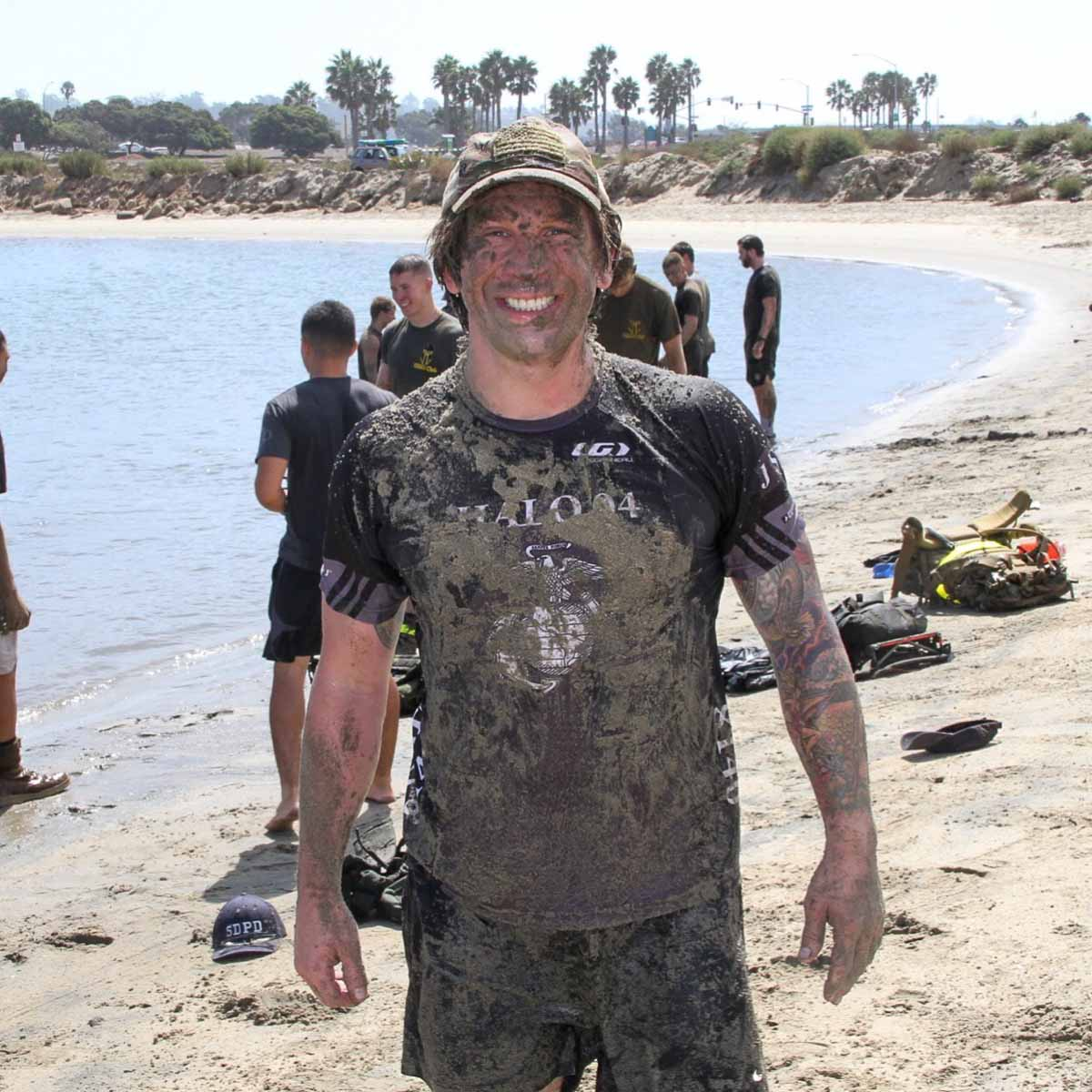 with Derek Abbey, Ph.D. man on beach covered in mud from running