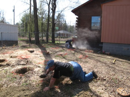 The piers are marked. One man is digging around a root to cut it out. The other man is cutting the sidewalk out. - Our Classic Manor New Day Cabin - Project Small House