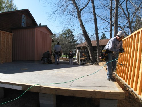 The flooring is put down and they are getting the walls into position. - Our Classic Manor New Day Cabin - Project Small House