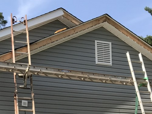 Decorative Vent, Ladder Jacks with Ladder as a Scaffold, The Soffit and Facsia - Installing the Vinyl Siding - Project Small House