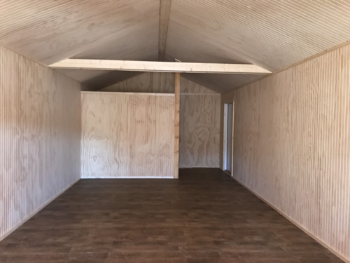 Inside has a vaulted ceiling. The sides are finished in bead board. There is a back door and a partial wall. - Clearance 14 x 38 Log Cabin – Project Small House